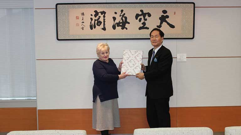 Angela receiving a gift from Governor Hamada